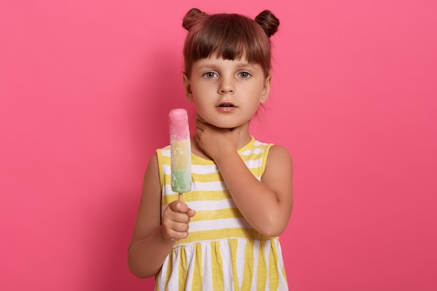 Enfant de sexe féminin mignon posant sur un mur rose tenant de la crème glacée