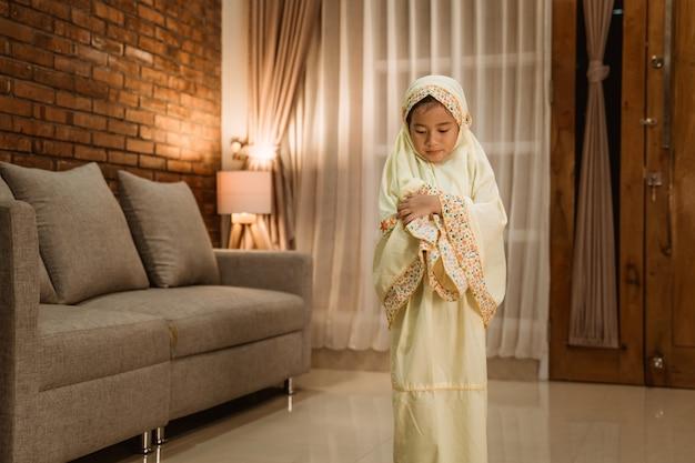 Enfant de sexe féminin musulman priant à la maison
