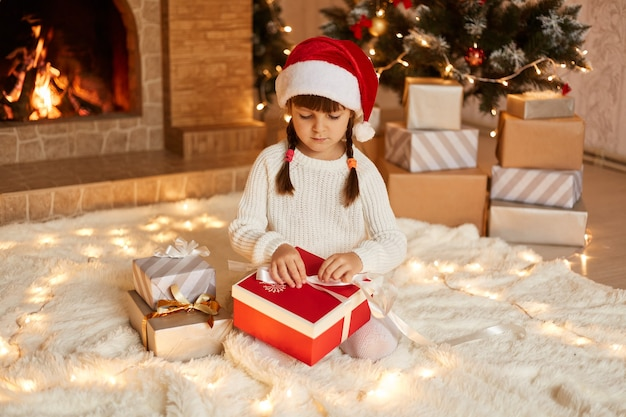 Enfant de sexe féminin optimiste portant un pull blanc et un chapeau de père noël, ouvrant une boîte-cadeau, ayant une expression faciale concentrée, assis sur le sol près de l'arbre de noël, des boîtes à cadeaux et une cheminée.
