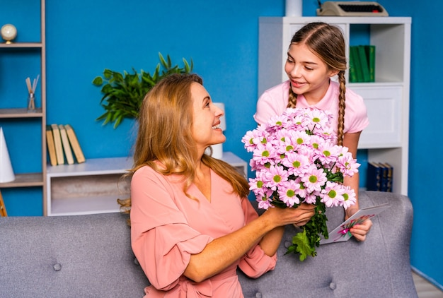 Enfant De Sexe Féminin Présentant Des Fleurs à Sa Mère à La Maison, Heureux Moments De La Vie Domestique Photo Premium