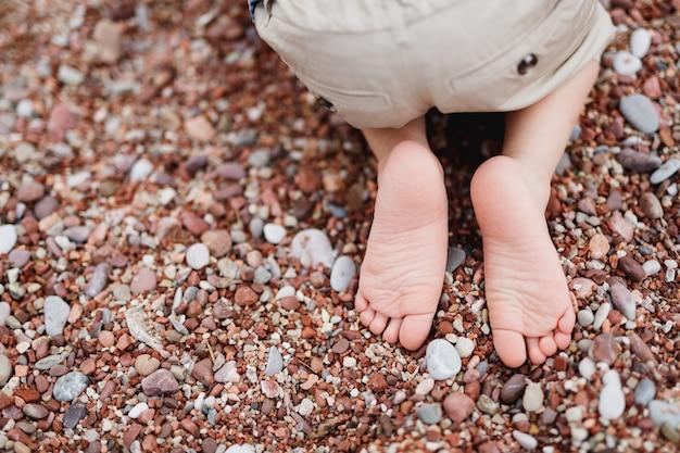 Enfant en short léger court est assis sur ses genoux sur une plage de galets libre