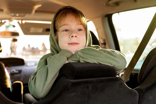Enfant smiley à l'intérieur de la voiture lors d'un voyage sur la route