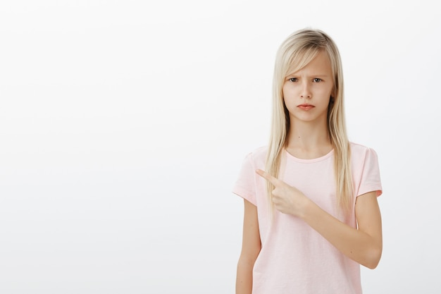 Enfant sombre déçu pointant vers la gauche