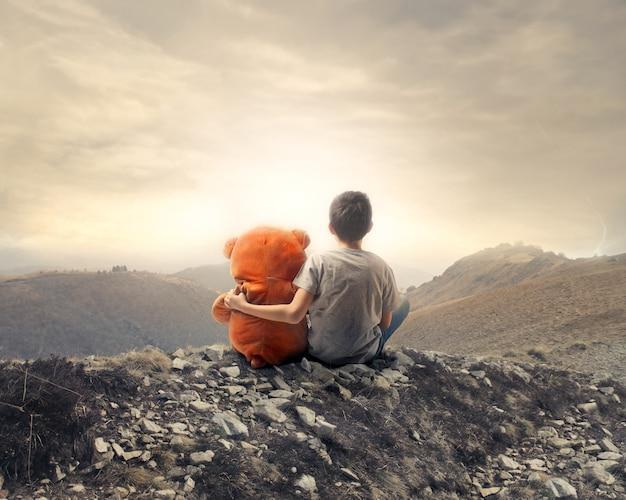 Enfant avec son ours sur le rocher