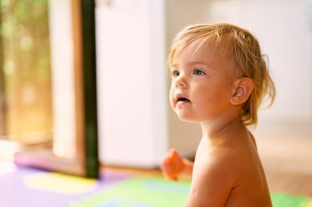 Enfant souriant assis sur un tapis coloré par terre dans la chambre