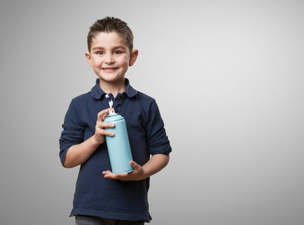 Enfant souriant avec une bombe aérosol