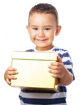 Enfant souriant avec un cadeau d'or