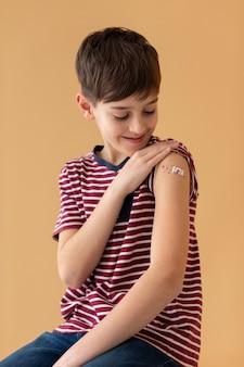 Enfant souriant de coup moyen après le vaccin