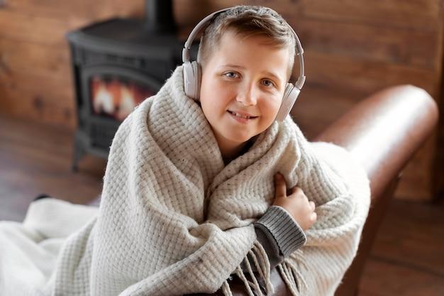Enfant souriant de coup moyen portant des écouteurs