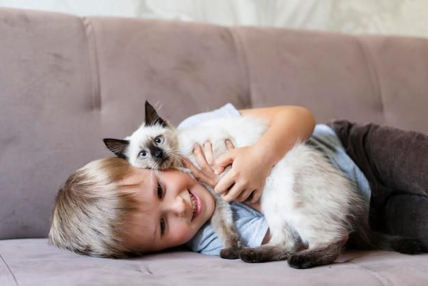 Enfant souriant de coup moyen tenant un chat mignon