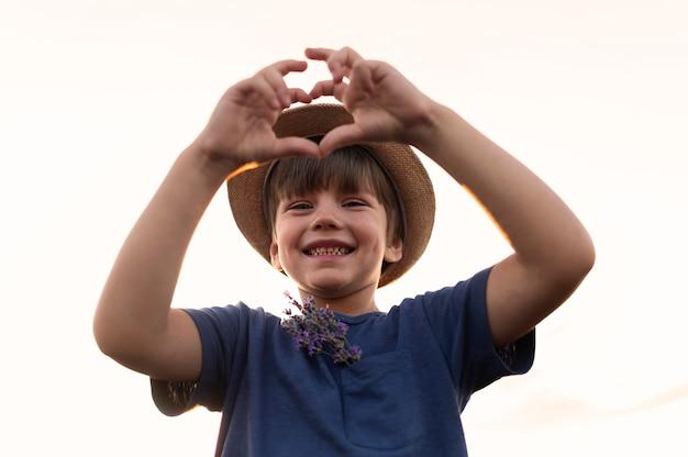 Enfant Souriant à Faible Angle Posant Photo gratuit