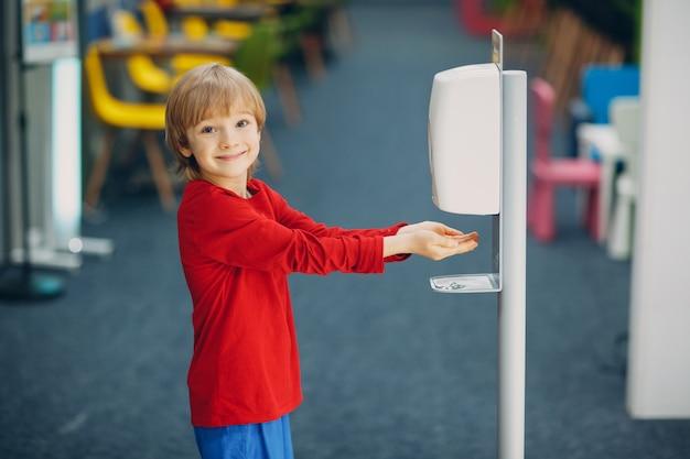 Enfant souriant garçon kid à l'aide d'un distributeur automatique de gel d'alcool pulvérisation sur les mains