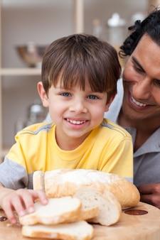 Enfant souriant, manger du pain avec son père