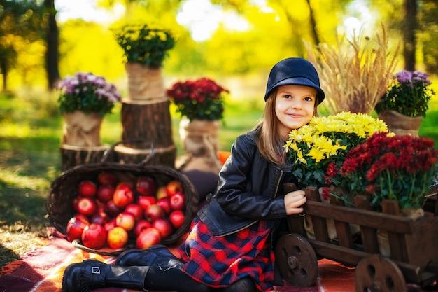 Enfant souriant avec panier de pommes rouges, assis dans un parc en automne