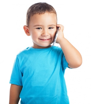 Enfant souriant avec un téléphone à son oreille