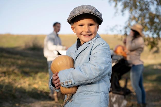 Enfant souriant tenant un coup moyen de citrouille