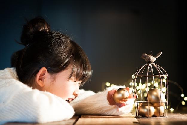 L'enfant souriant tient un œuf de pâques.