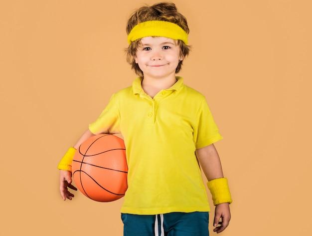Enfant de sport. enfant souriant avec ballon de basket. activités pour enfants. petit basketteur. équipement de sport.