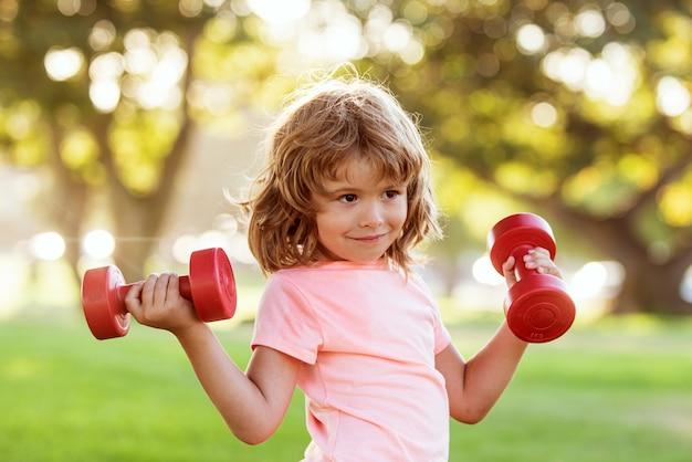 Enfant sportif avec haltère dans le parc. sport pour enfants. garçon exerçant en plein air. mode de vie actif et sain.