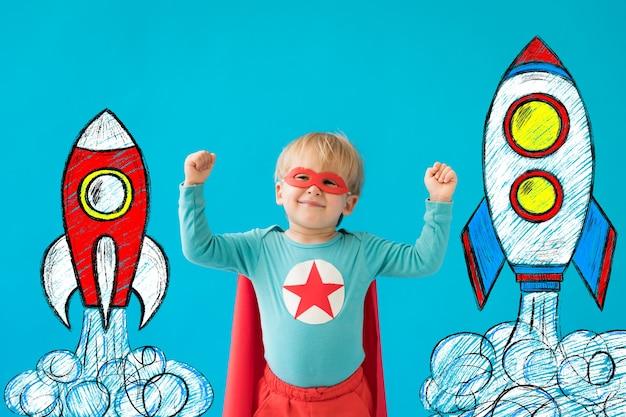 Enfant de super héros contre le mur bleu.