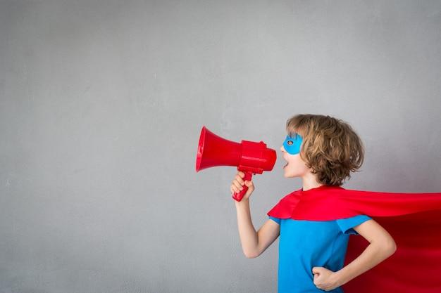 Enfant de super-héros. kid prétend être homme d'affaires. concept de réussite, de créativité et d'imagination