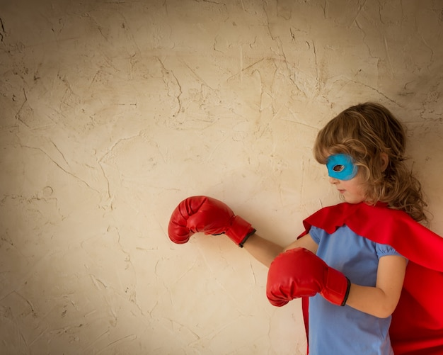 Enfant de super-héros vêtu d'une cape rouge, de gants de boxe et d'un masque bleu sur fond de mur grunge