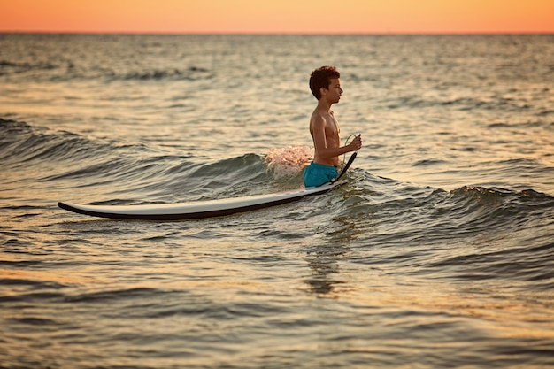 Enfant surfant sur une plage tropicale