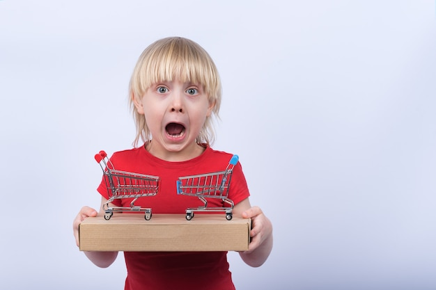 Enfant surpris avec boîte et deux petit panier sur un espace blanc. achat en ligne et livraison à domicile