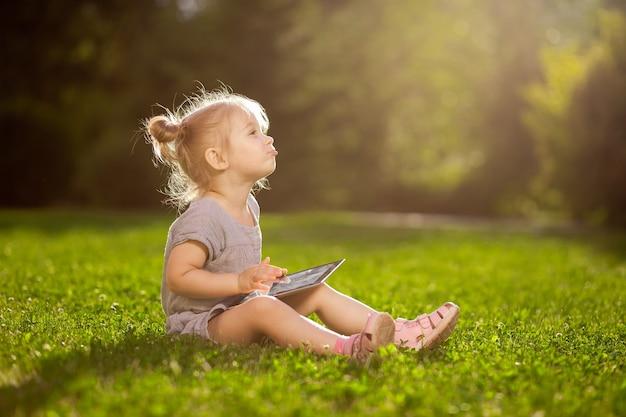 Enfant avec une tablette assis dans le parc