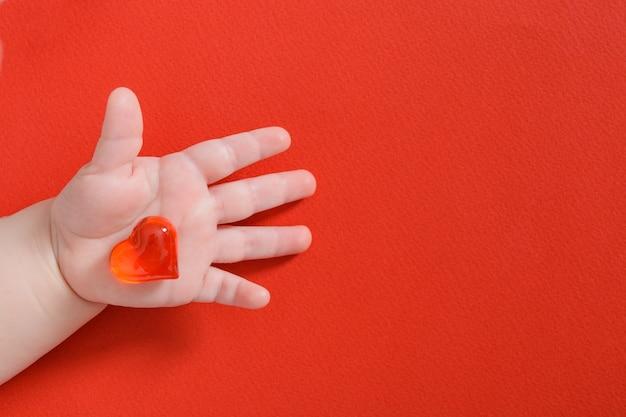 Enfant tenant coeur de verre isolé sur rouge