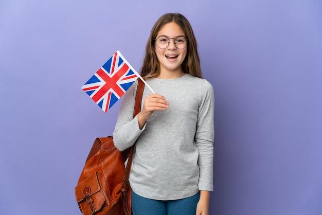 Enfant tenant un drapeau du royaume-uni sur fond isolé avec une expression faciale surprise