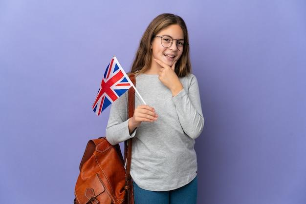 Enfant tenant un drapeau du royaume-uni sur fond isolé heureux et souriant