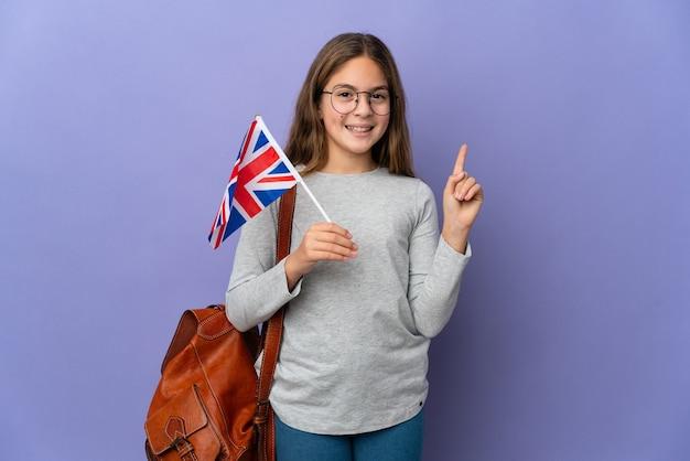 Enfant tenant un drapeau du royaume-uni sur fond isolé montrant et levant un doigt en signe du meilleur