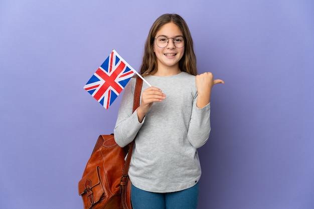 Enfant tenant un drapeau du royaume-uni sur fond isolé pointant vers le côté pour présenter un produit