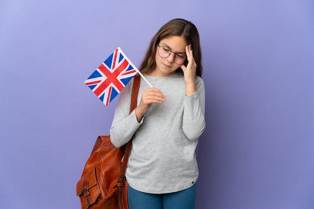 Enfant tenant un drapeau du royaume-uni sur un mur isolé avec des maux de tête