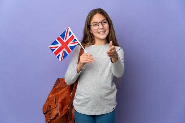 Enfant tenant un drapeau du royaume-uni sur un mur isolé se serrant la main pour conclure une bonne affaire