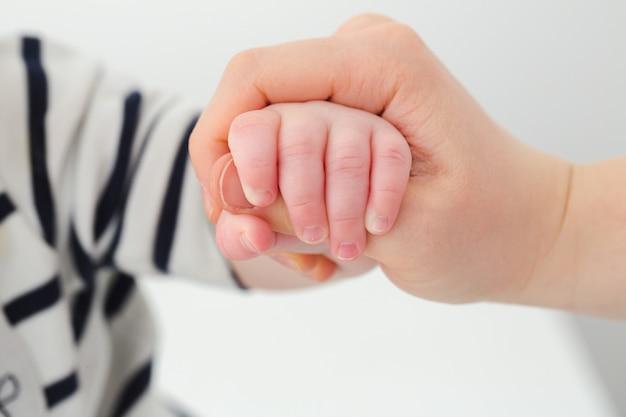 Un enfant tenant la main d'un parent