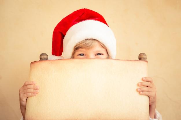 Enfant tenant le rouleau de papier de noël. concept de vacances de noël