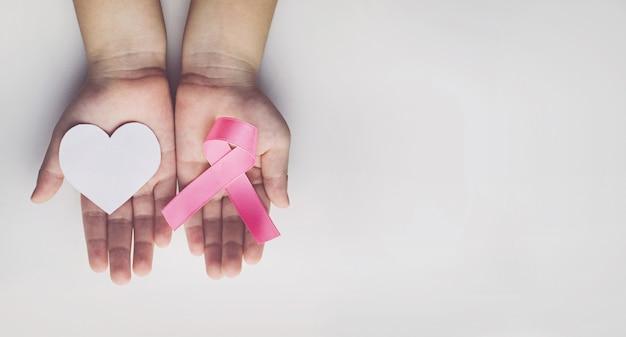 Enfant tenant un ruban rose. la sensibilisation au cancer du sein