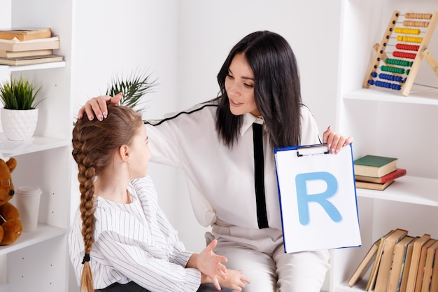 Enfant avec un thérapeute travaillant sur la prononciation et les sons ensemble assis dans la classe.