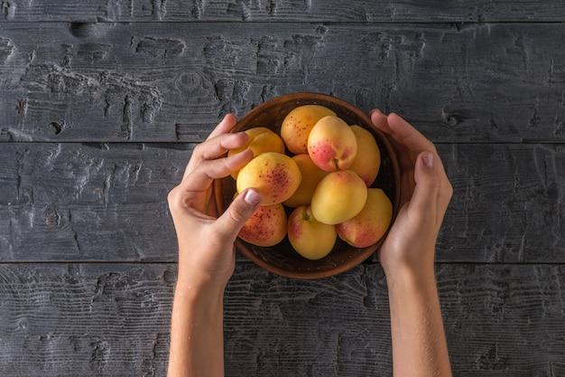 L'enfant tient un bol avec des abricots mûrs