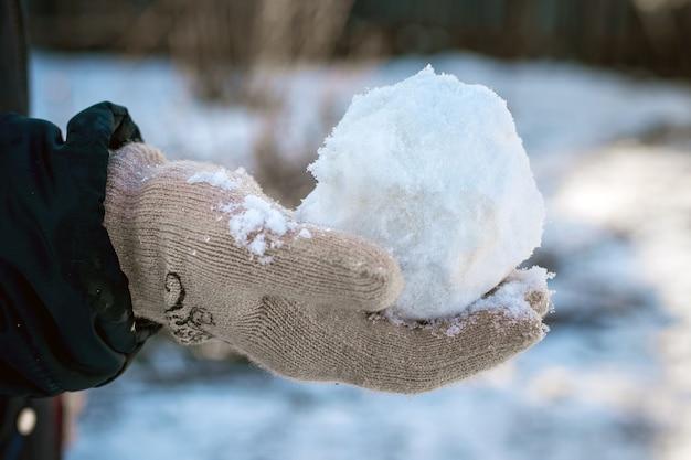 L'enfant tient une boule de neige dans sa main