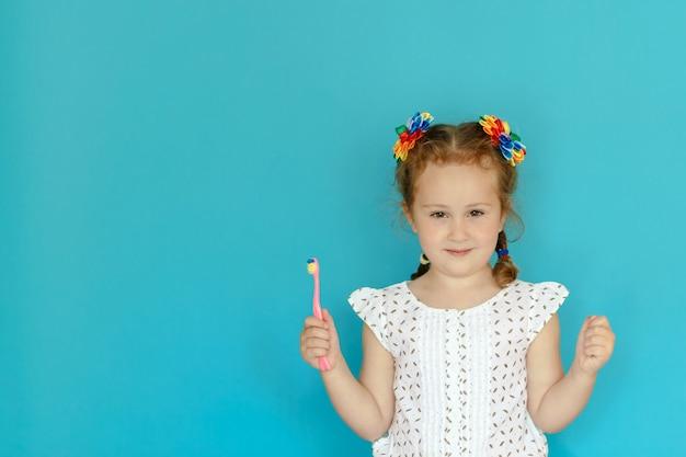 L'enfant tient une brosse à dents