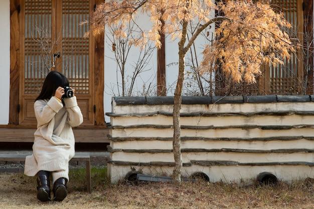 L'enfant tient une caméra entre les arbres.