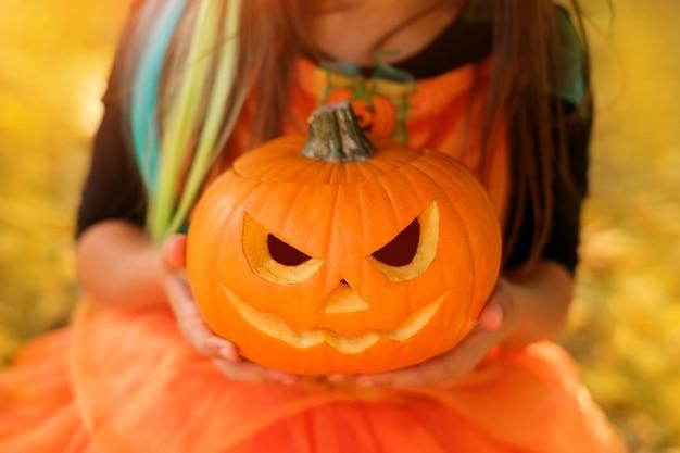 Un enfant tient une citrouille avec un sourire sinistre sculpté dans ses mains