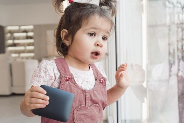 L'enfant tient une colonne à la main. l'enfant regarde par la fenêtre. portrait d'une jeune fille dans une robe d'été rose