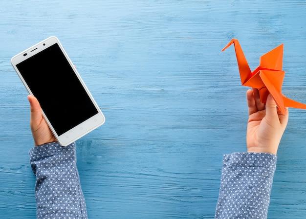 Enfant tient dans ses mains un téléphone et une grue en origami