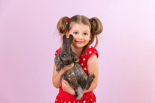 Un enfant tient un petit lapin dans ses mains. une fille avec un lapin sur un fond isolé.