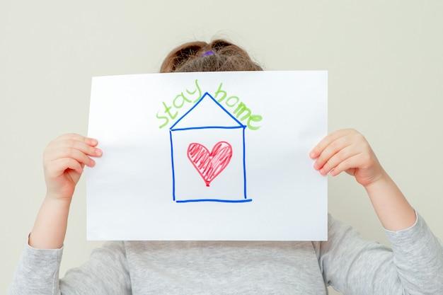 L'enfant tient une photo de la maison.