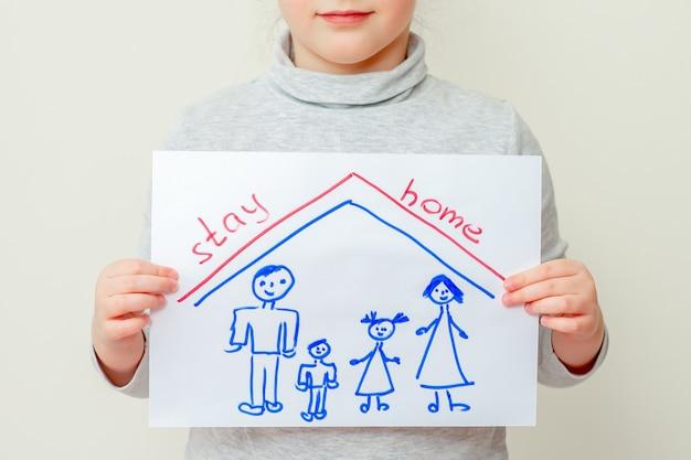 Un enfant tient une photo d'une silhouette de famille sous le toit et les mots restent à la maison